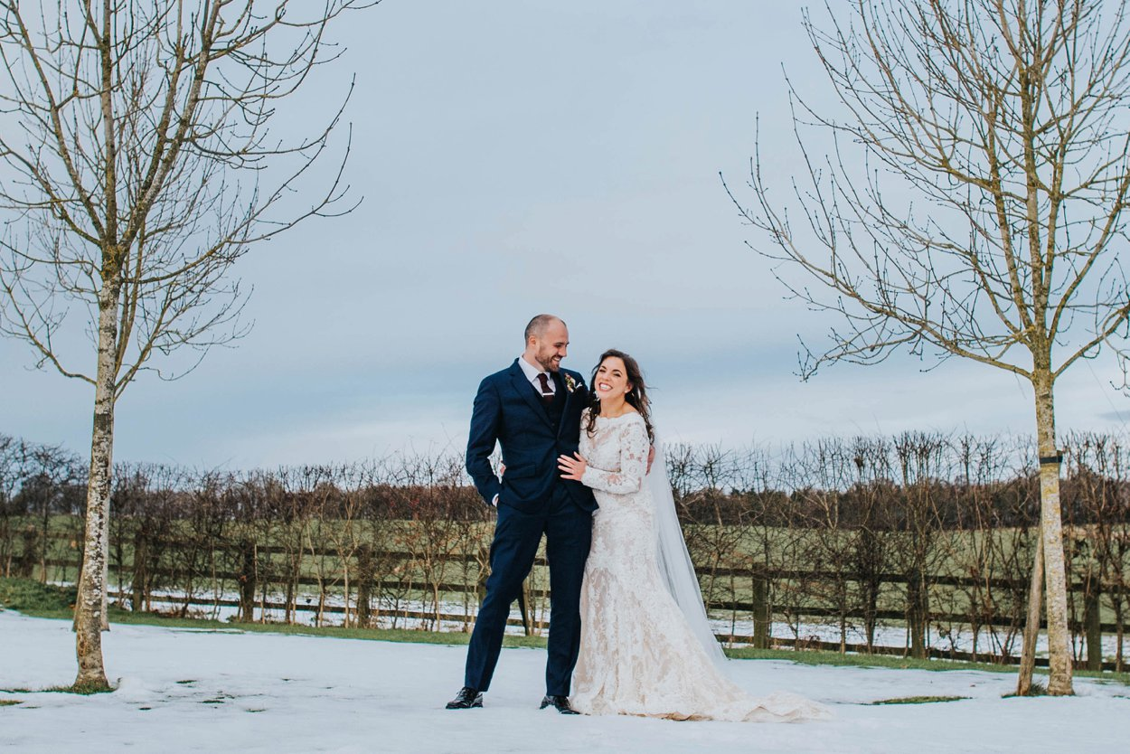 bride and groom standing in snow on wedding day cripps stone barn