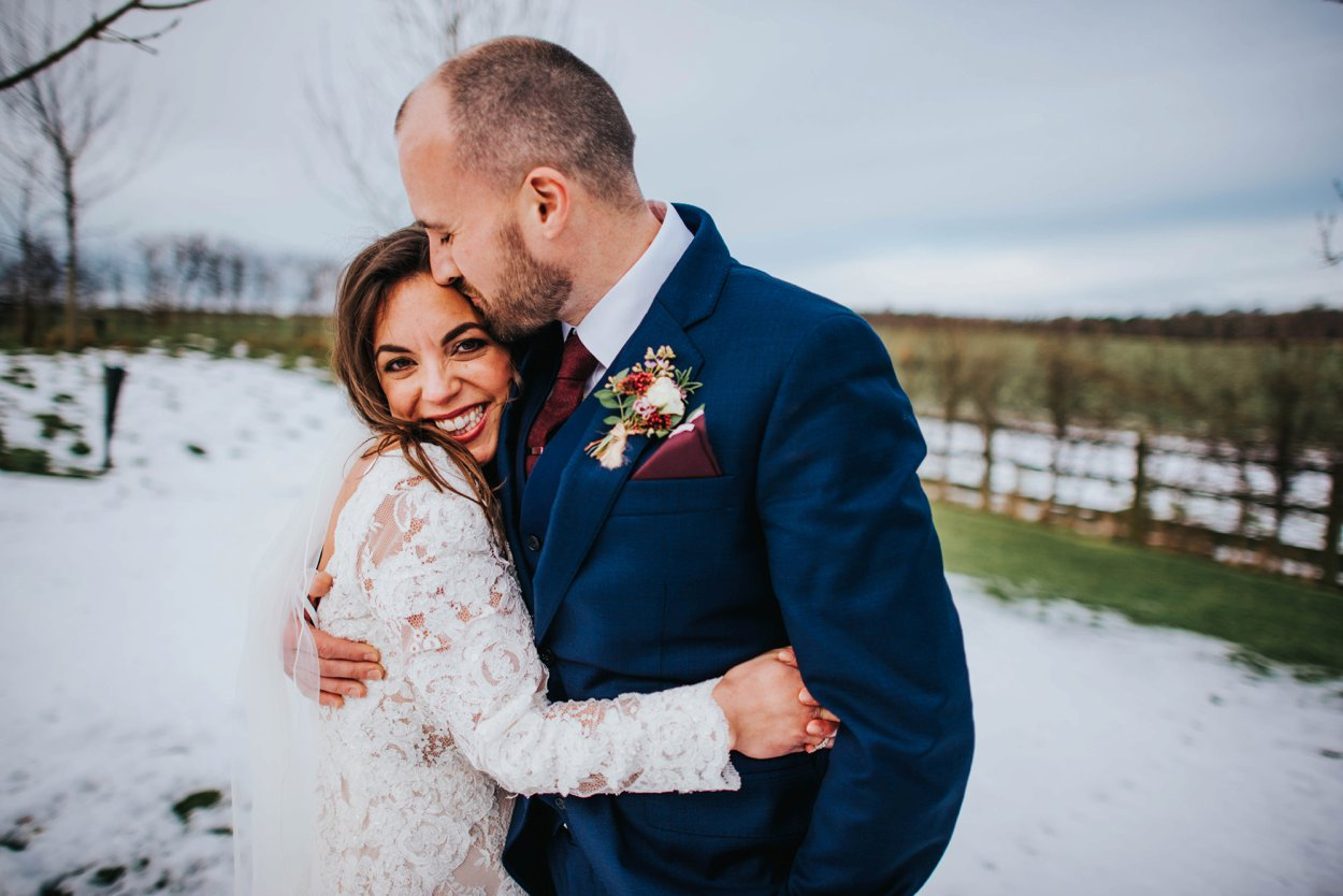 bride and groom standing in snow on wedding day