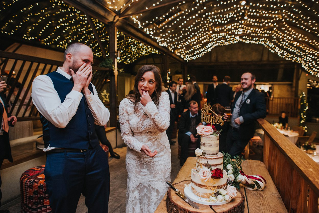 bride and groom laughing cutting cake infont of fairy lights