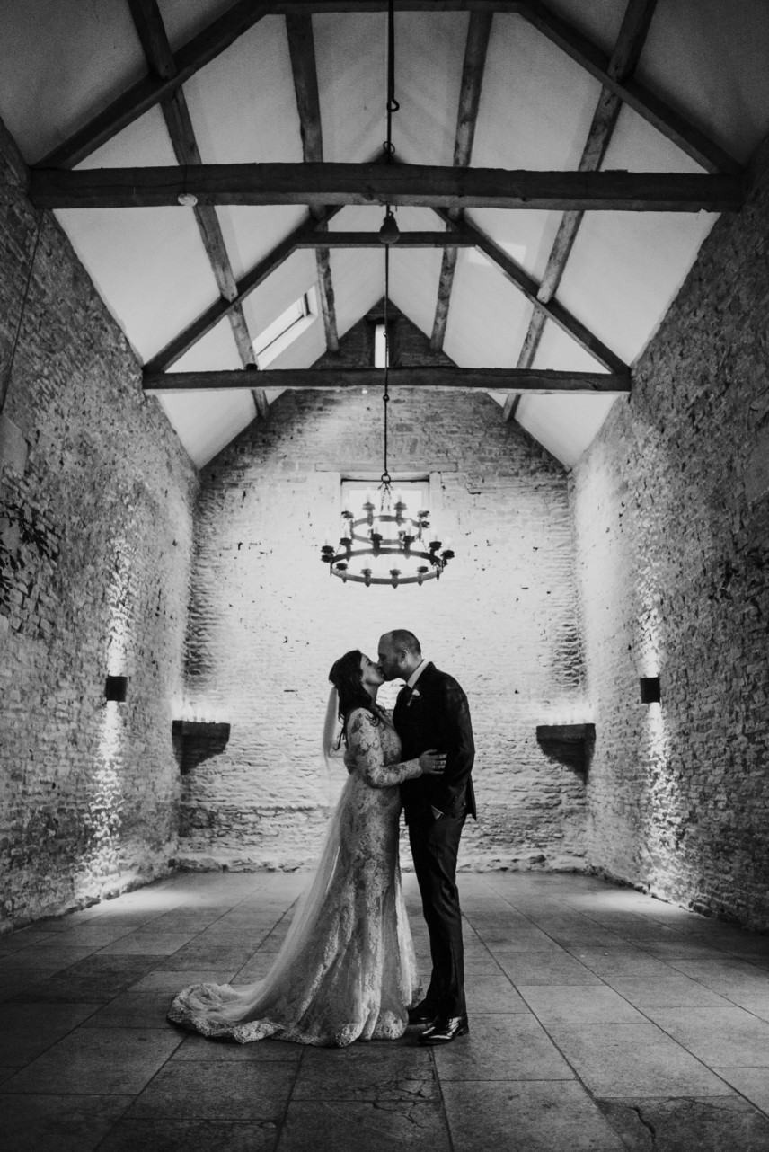 bride and groom kissing in cripps stone barn