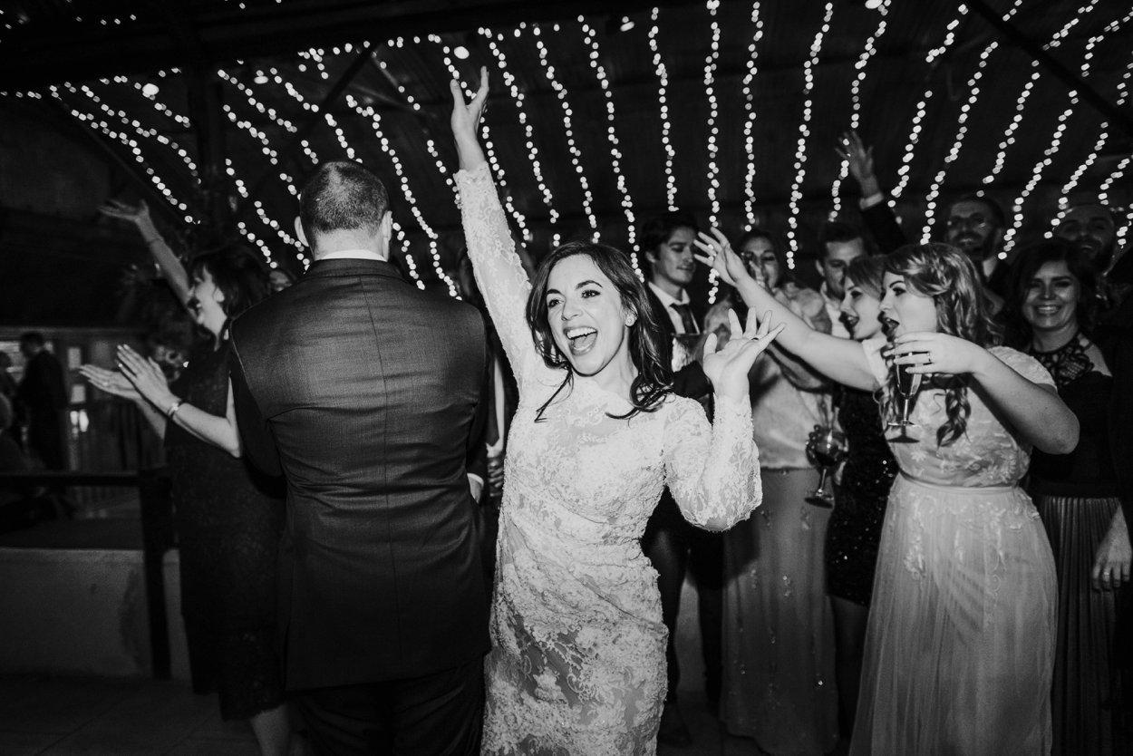 bride waving arms around on dance floor