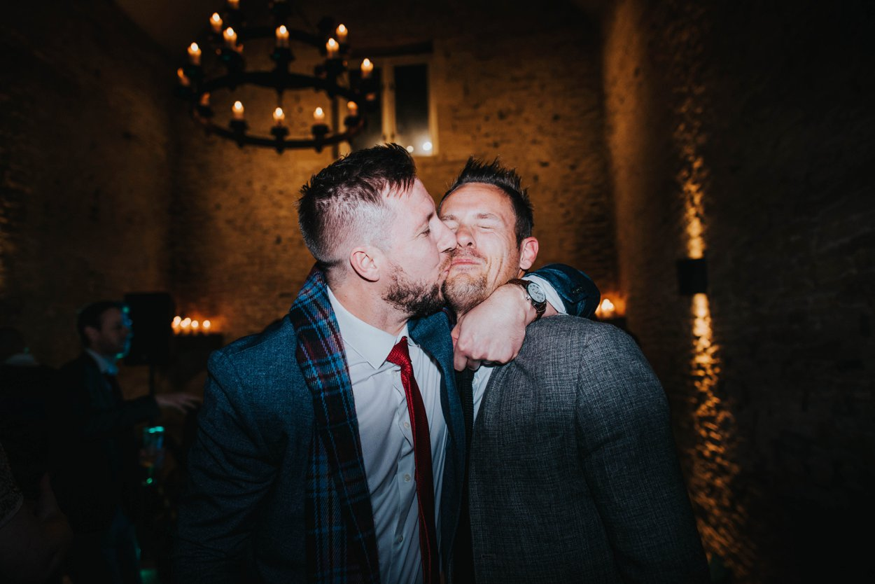 two men kissing at a wedding