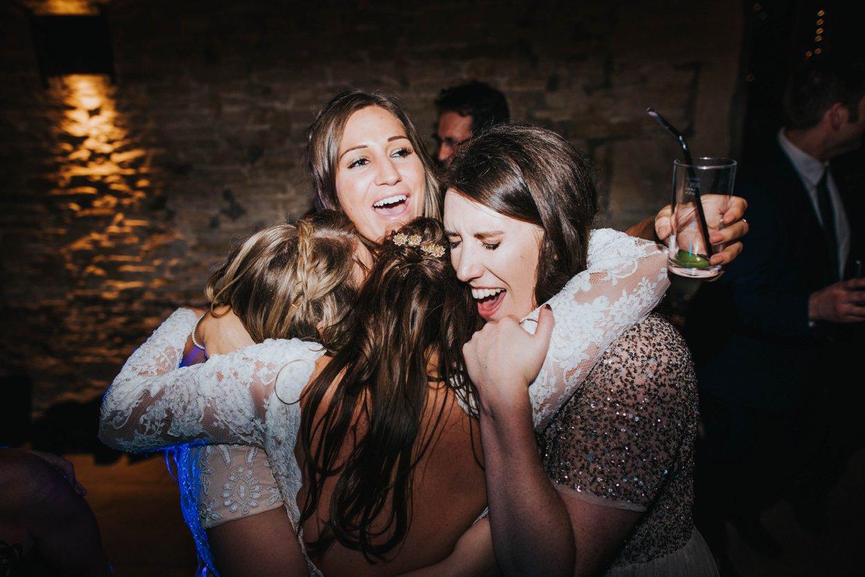 bride and bridesmaids huggung