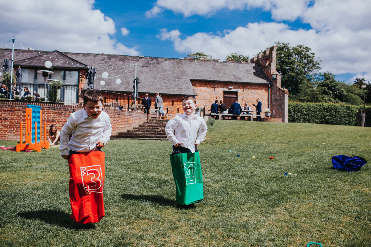 boys playing sack races at wedding