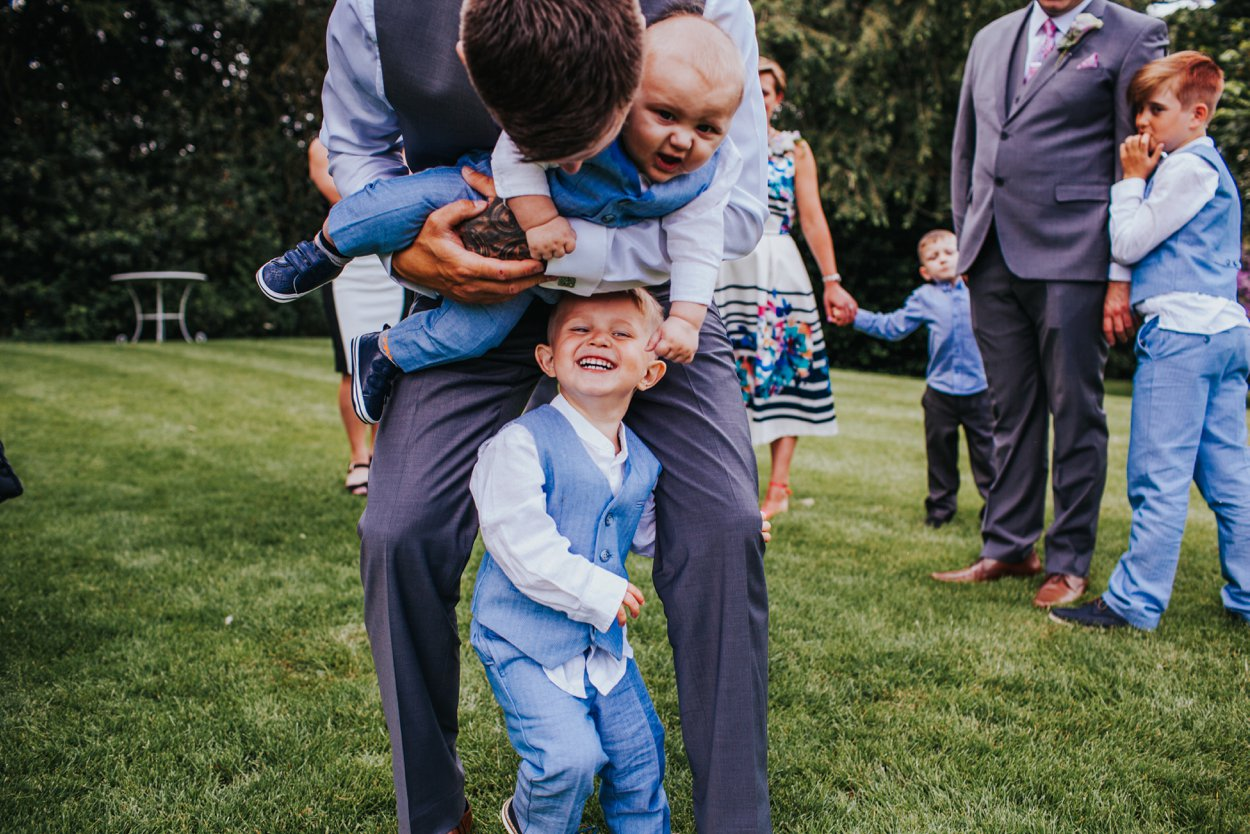 man hugging kids at wedding