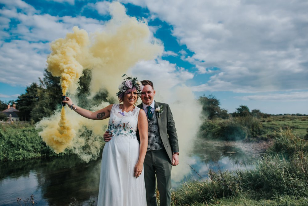 bride and groom holding smokebomb sopley mill