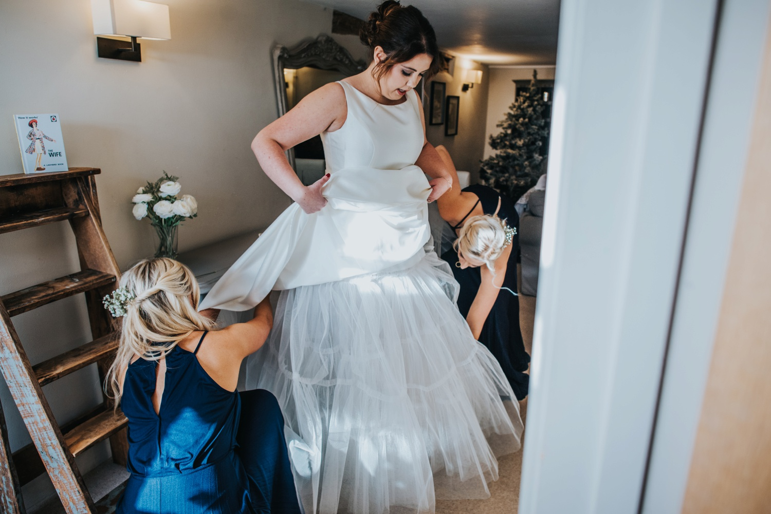 bride putting her dress on at Sopley Mill