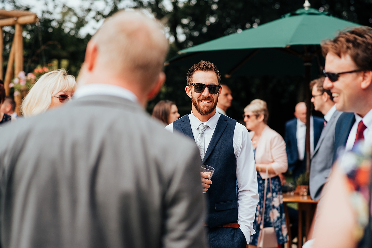 man in suit wearing sunglasses at wedding