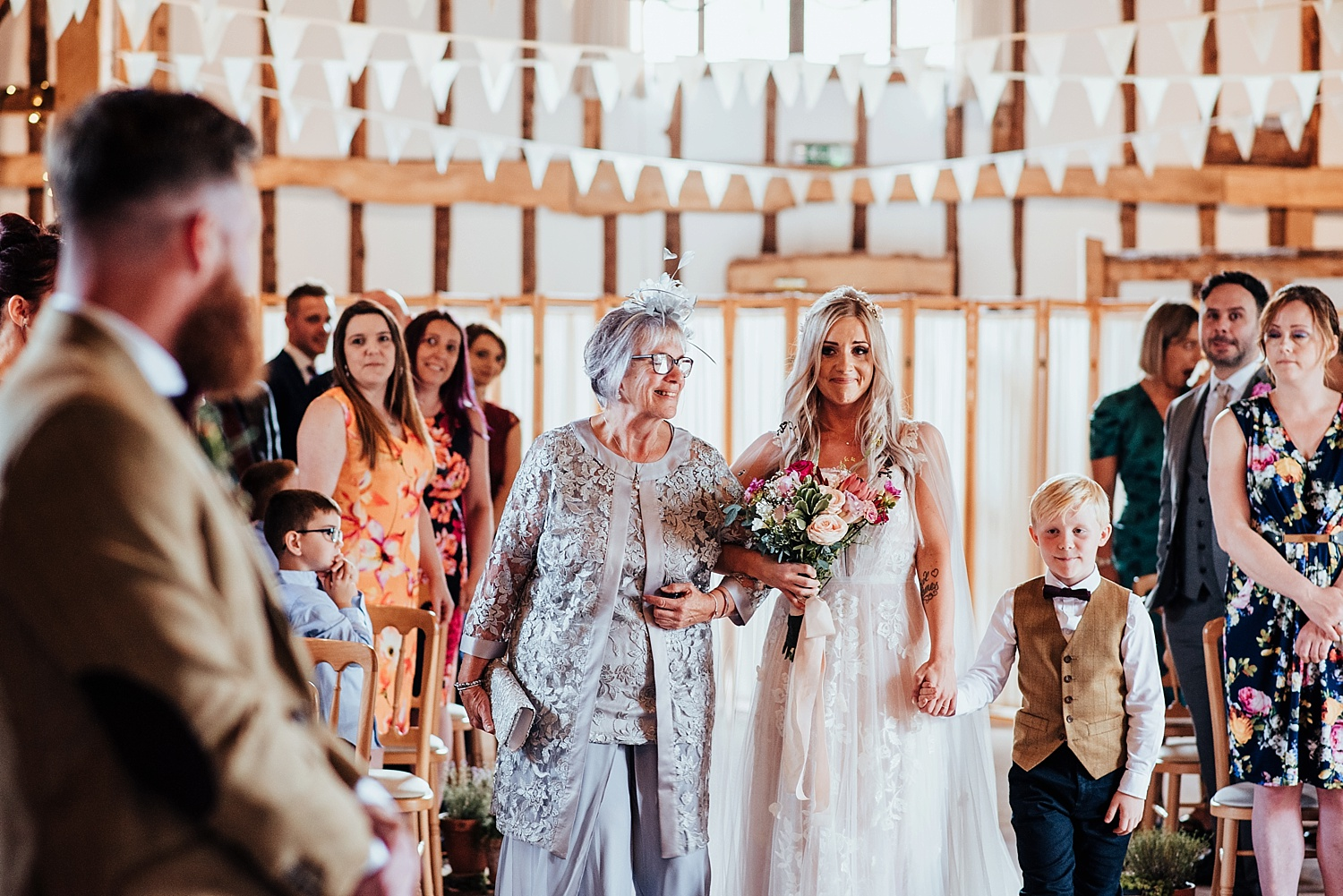 boho bride with loose curls in hair walking down isle with mother and son clock barn