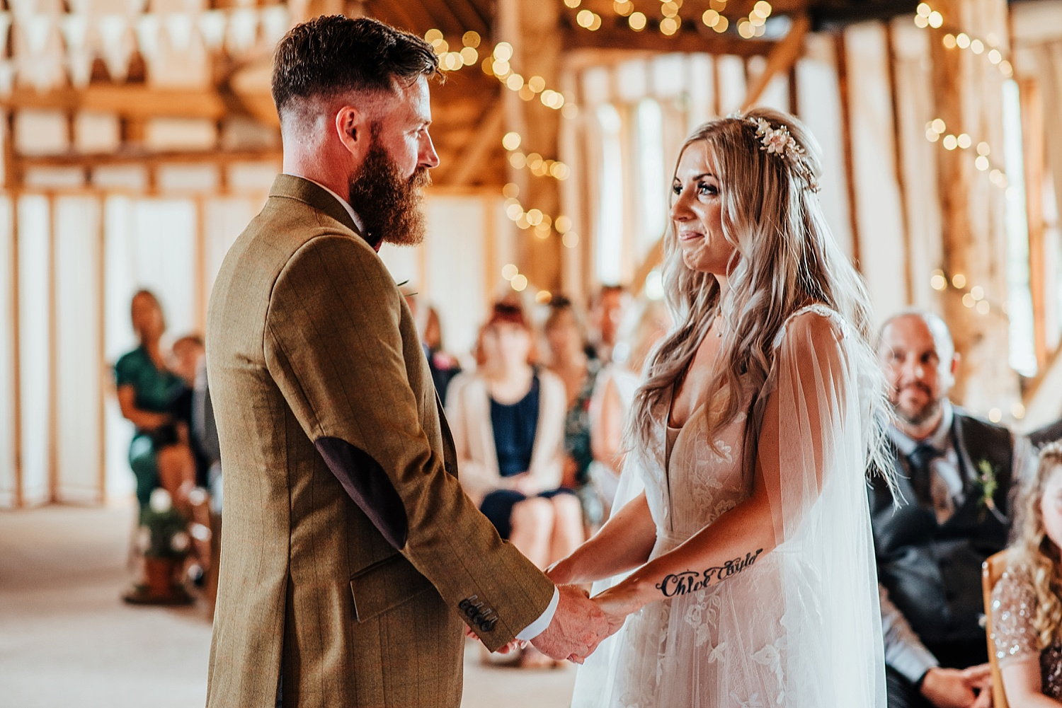 boho bride and groom holding hands at clock barn
