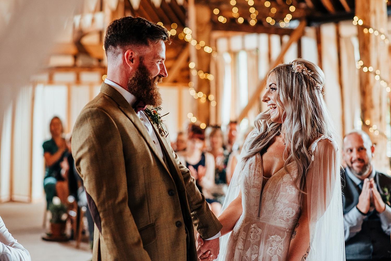 boho bride laughing saying i do at clock barn