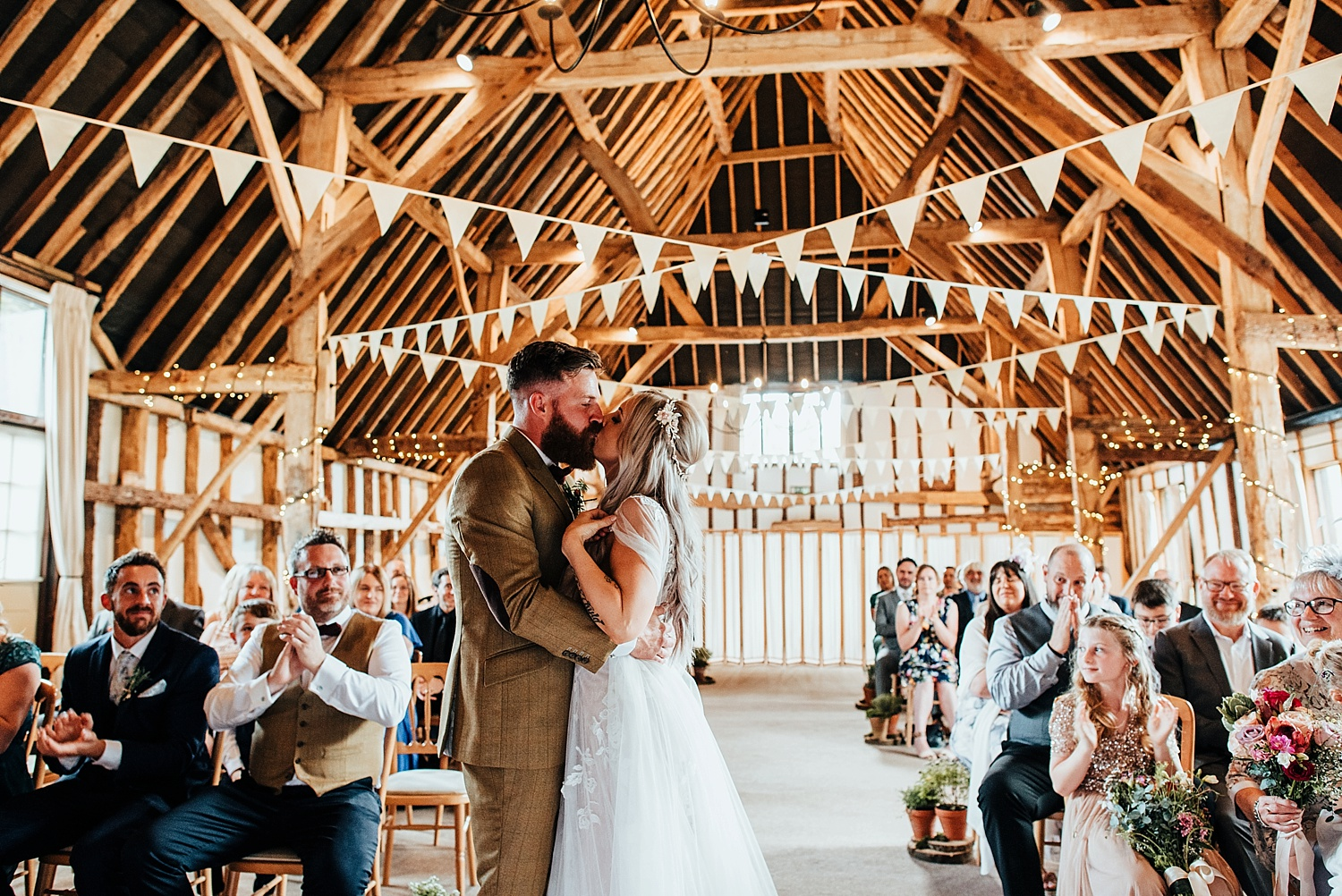 bride and groom kissing in clock barn surrounded by bunting