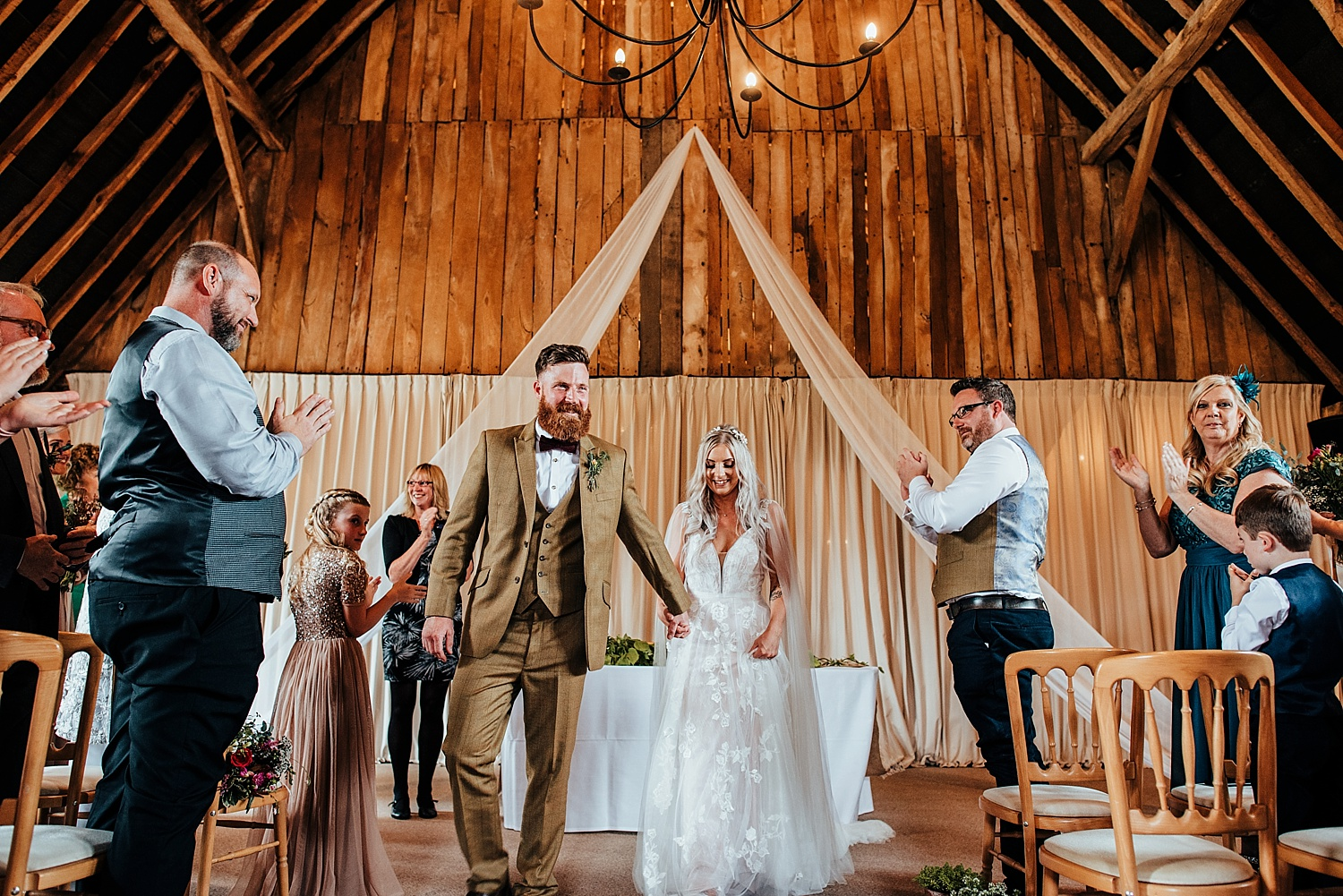 boho bride with caped dress holding grrom in brown tweed suits hand