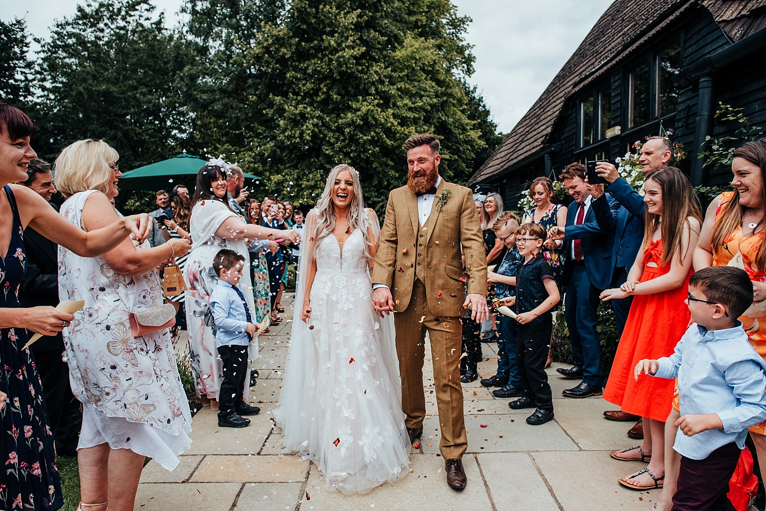 bride and groom leaving clock barn with hands in the air
