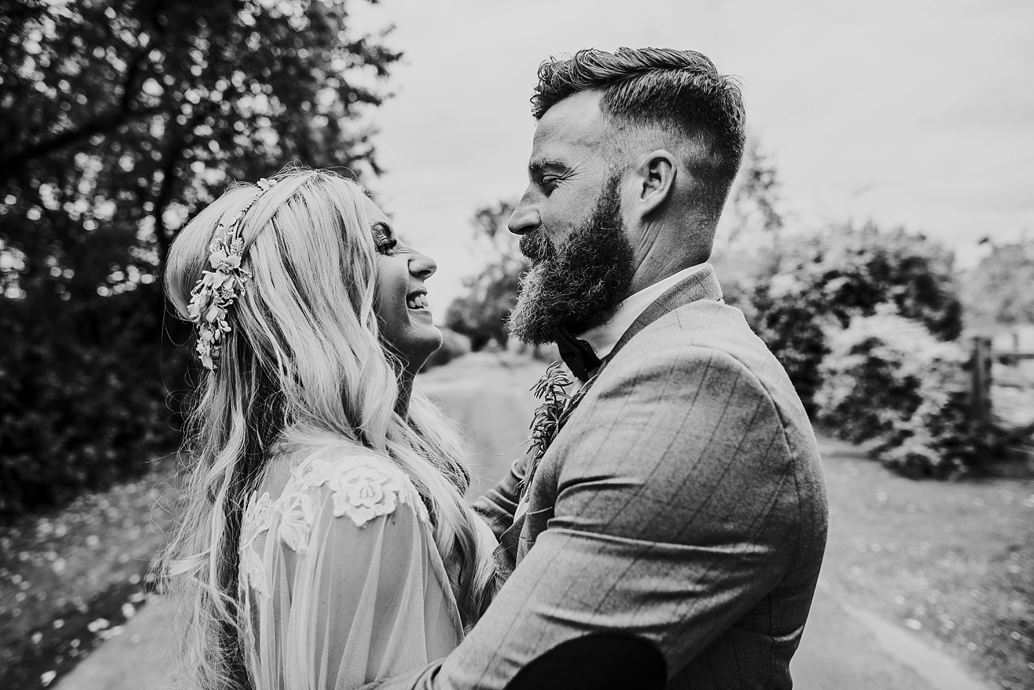 boho bride with caped wedding dress kissing groom in brown tweed suit outside clock barn