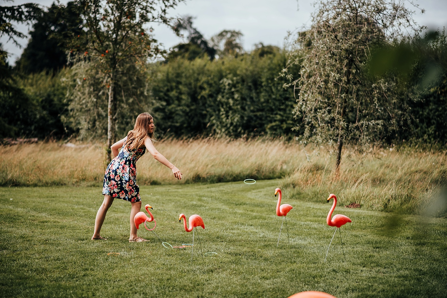 girl in floral dress playing hoopla on flamingos at clock barn