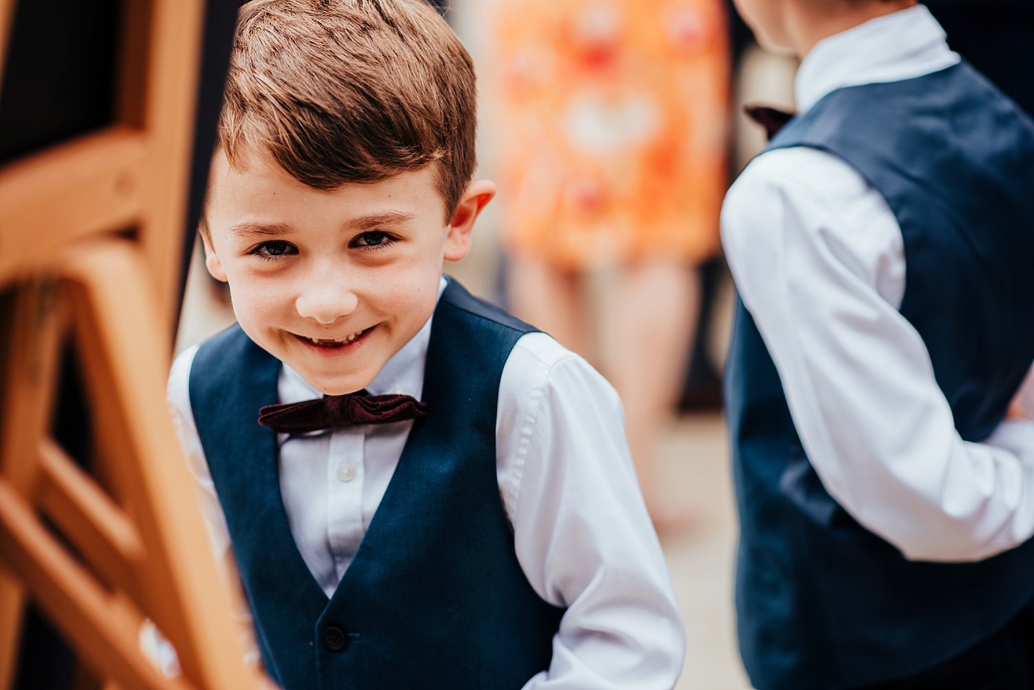 young boy in suit and bowtie smiling at camera
