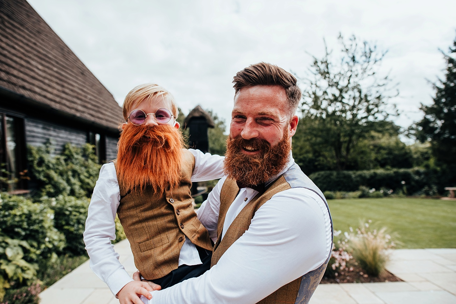 father with beard holding son with a dress up beard