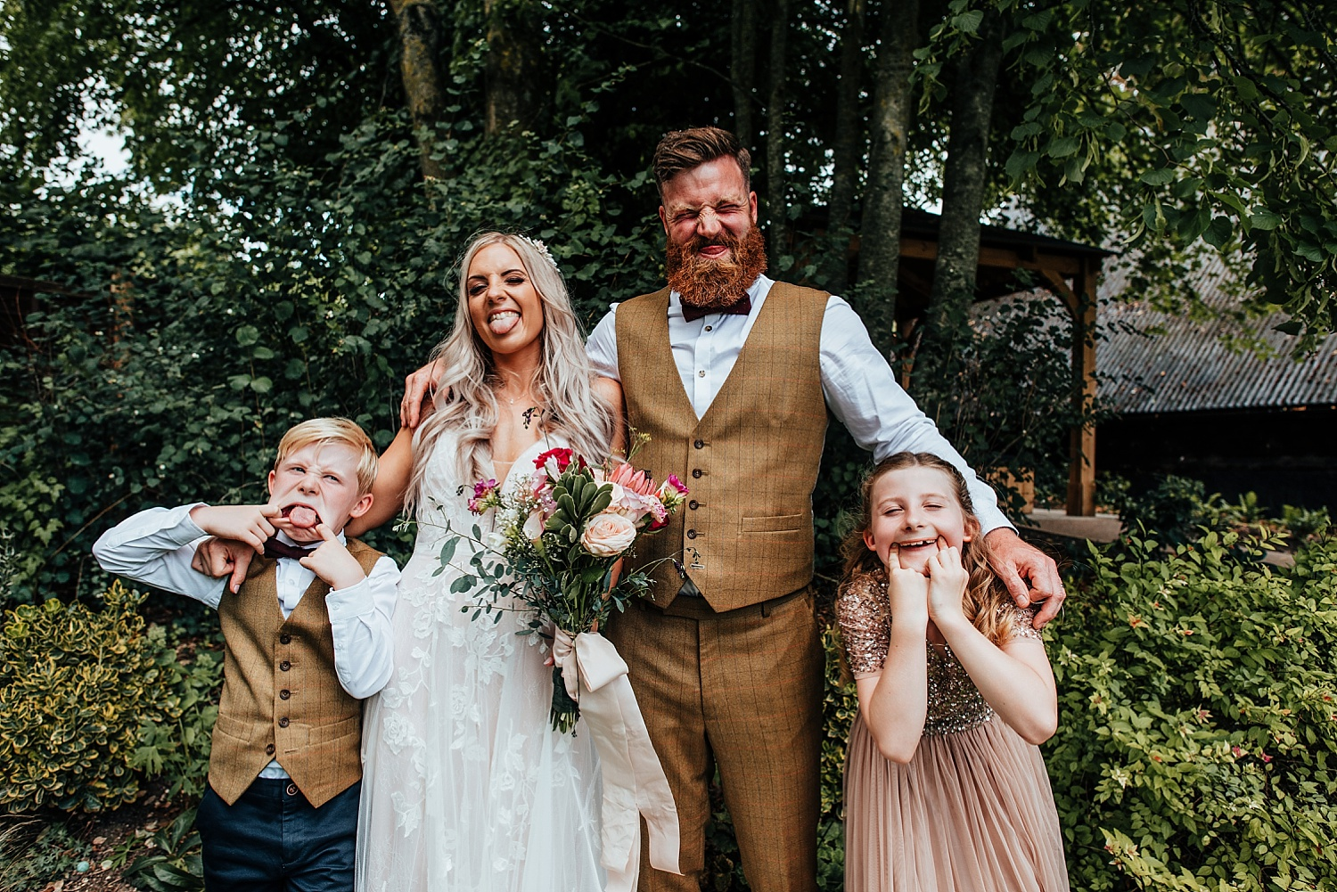 boho bride and grrom with children pulling silly faces