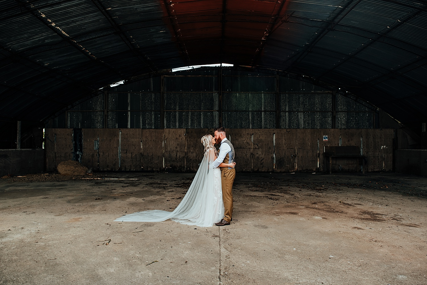 boho bride standing in an open barn with groom in brown tweed suit at clock barn