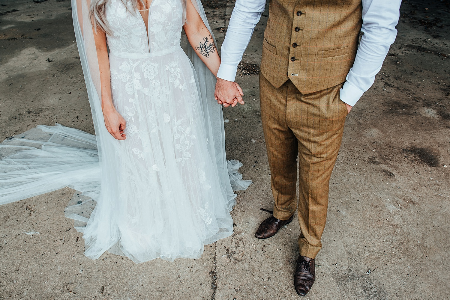 tatooed boho bride wearing caped wedding dress holding hands with groom