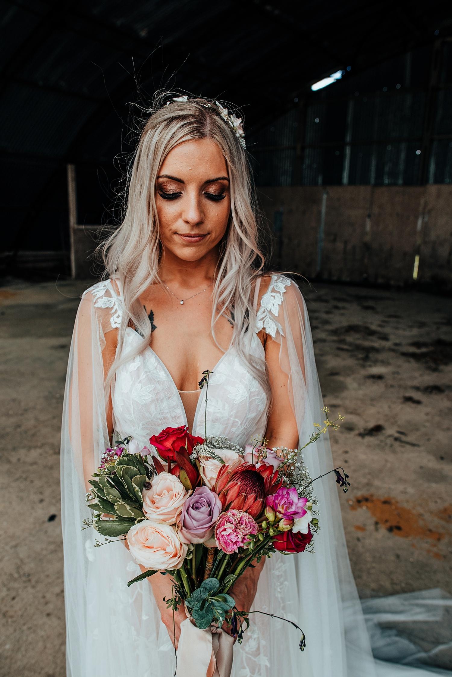 boho bride wearing caped wedding dress holding flowers in an open barn clock barn