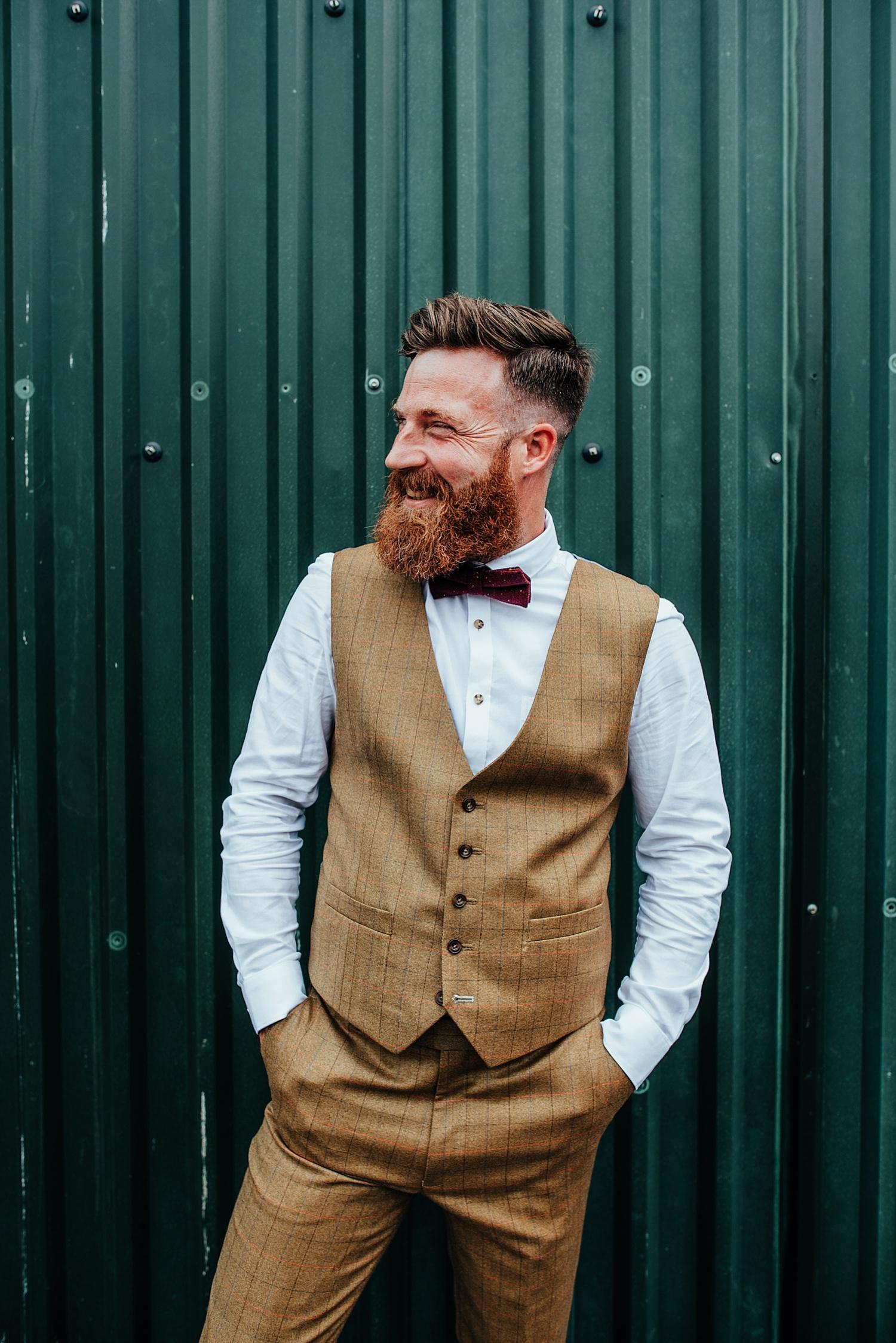 smiling groom wearing tweed brown suit at clock barn