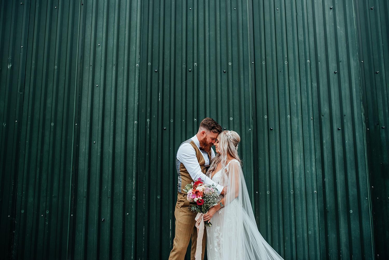 boho bride walking hand in hand with groom in brown tweed suit at clock barn