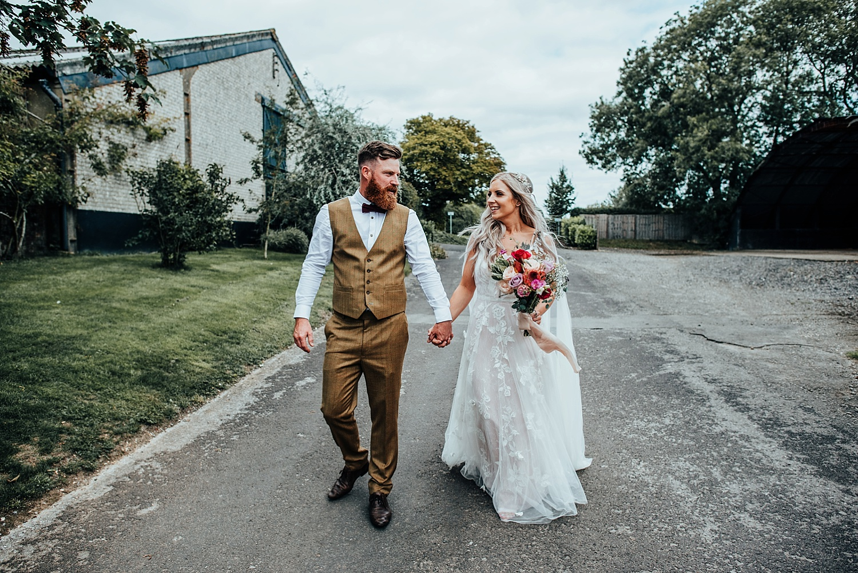 boho bride standing with groom in brown tweed suit at clock barn