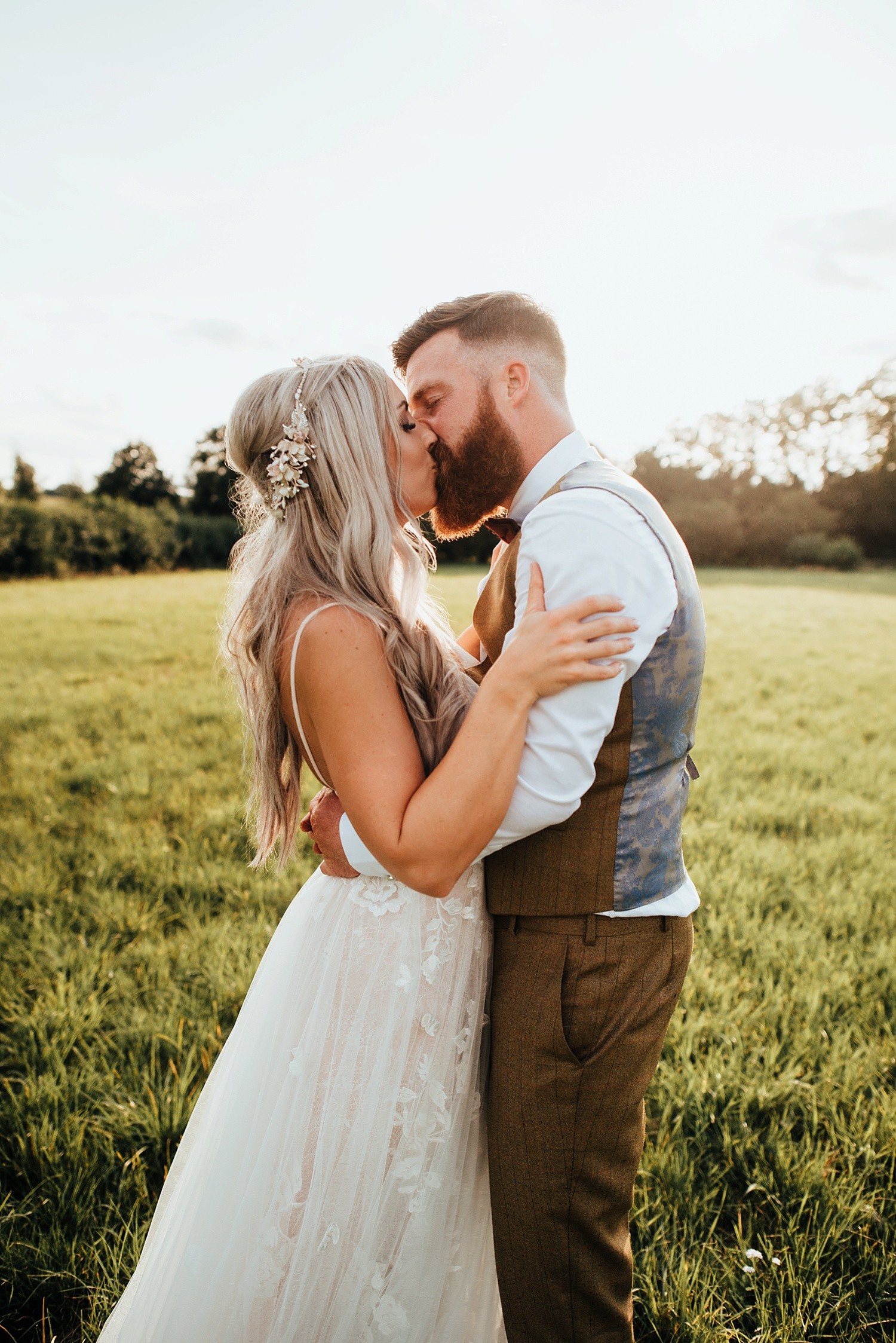 bride and groom hugging in field at sunset clock barn