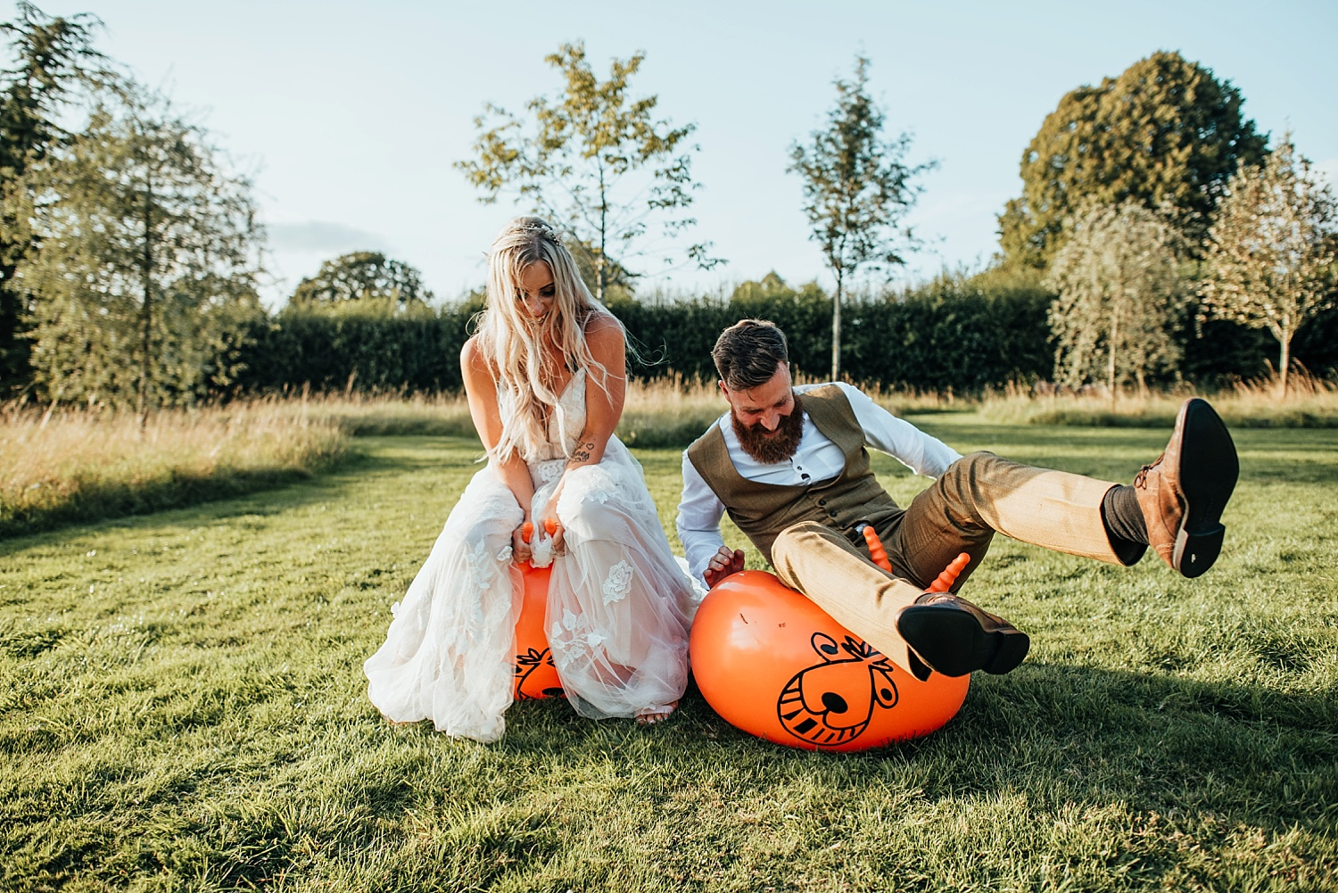 bride anf grrom falling off orange space hoppers in field at clock barn