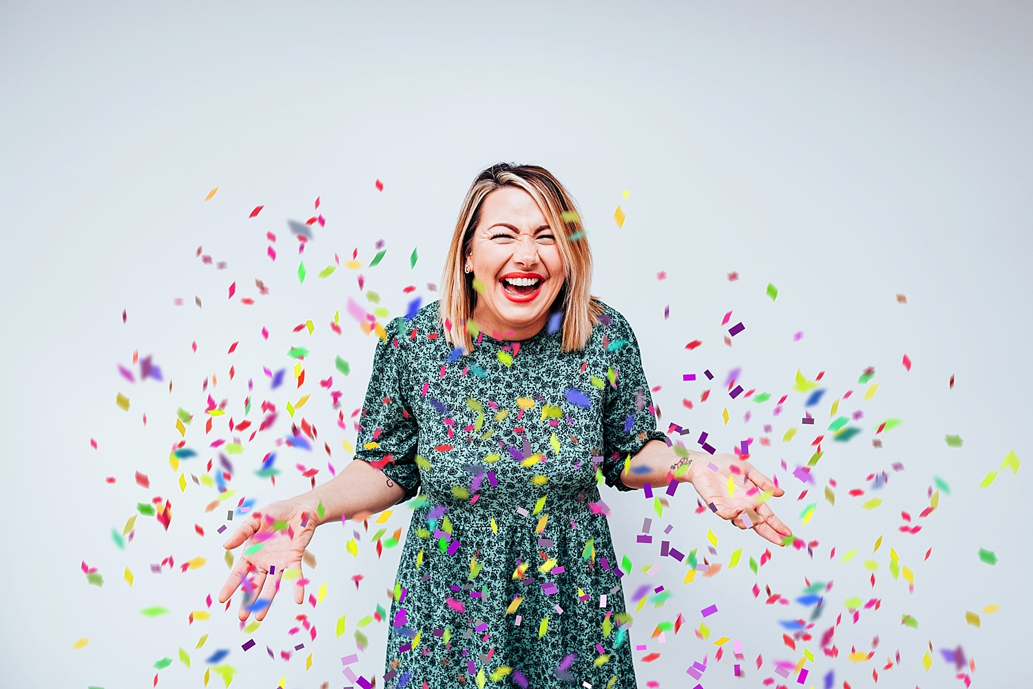 woman in green dress standing by white wall throwing confetti