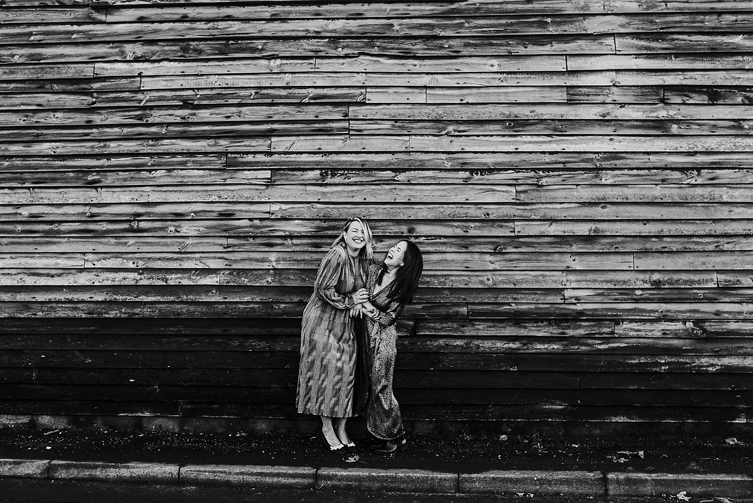 2 women in dresses laughing in front of barn