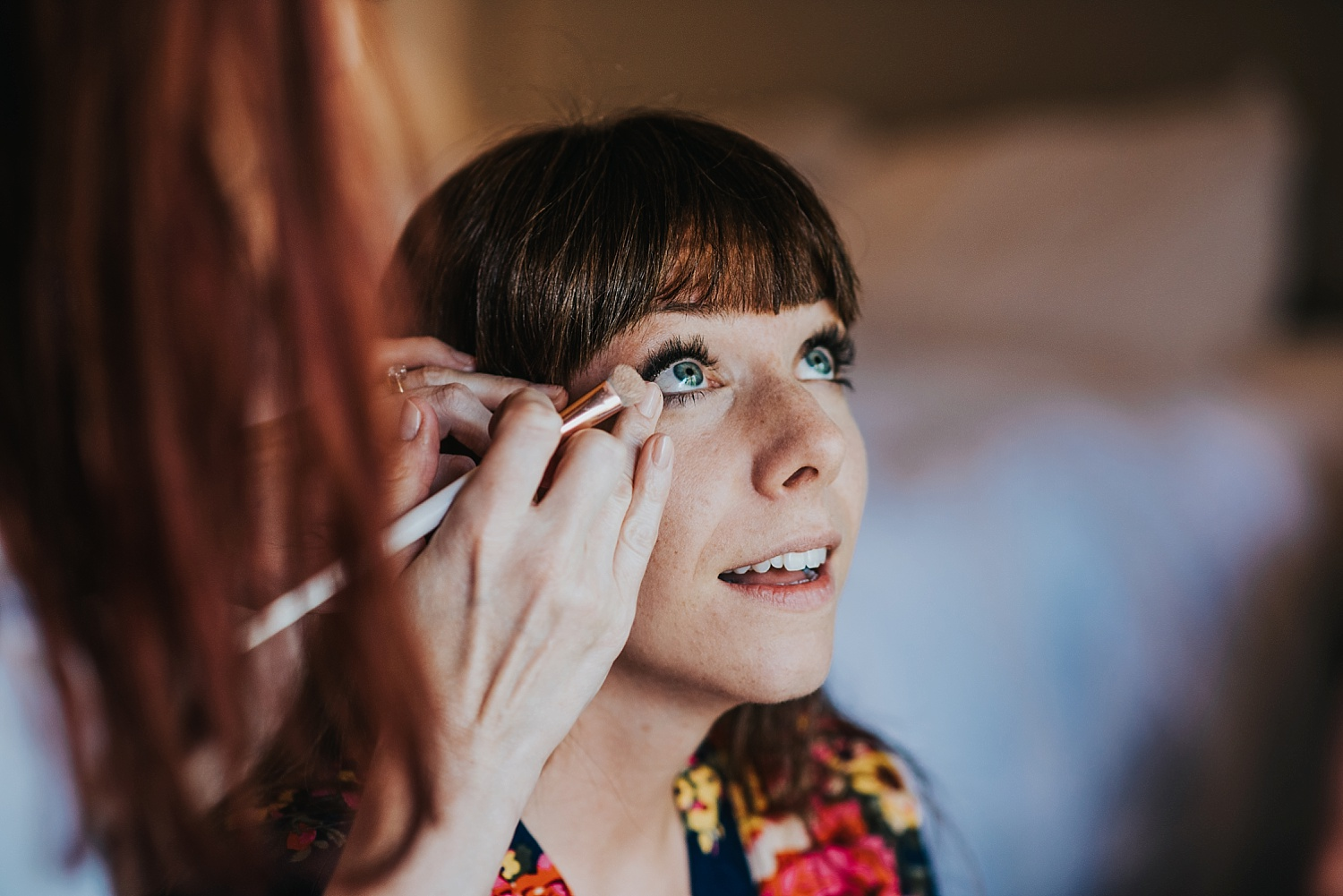 bride with blue eyes having make up done