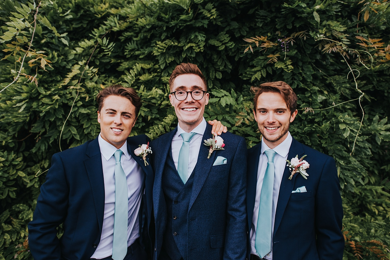 groom and groomsmen standing together on wedding day
