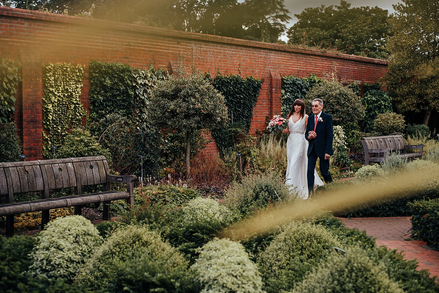 bride and grandad walking through the walled garden RHS Wisley
