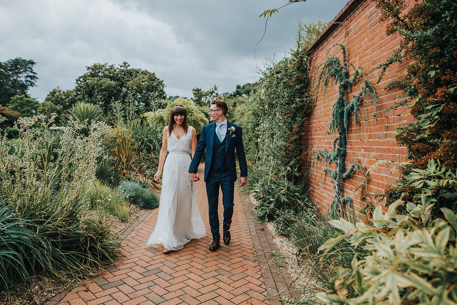 bride and groom walking hand in hand in walled garden RHS Wisley