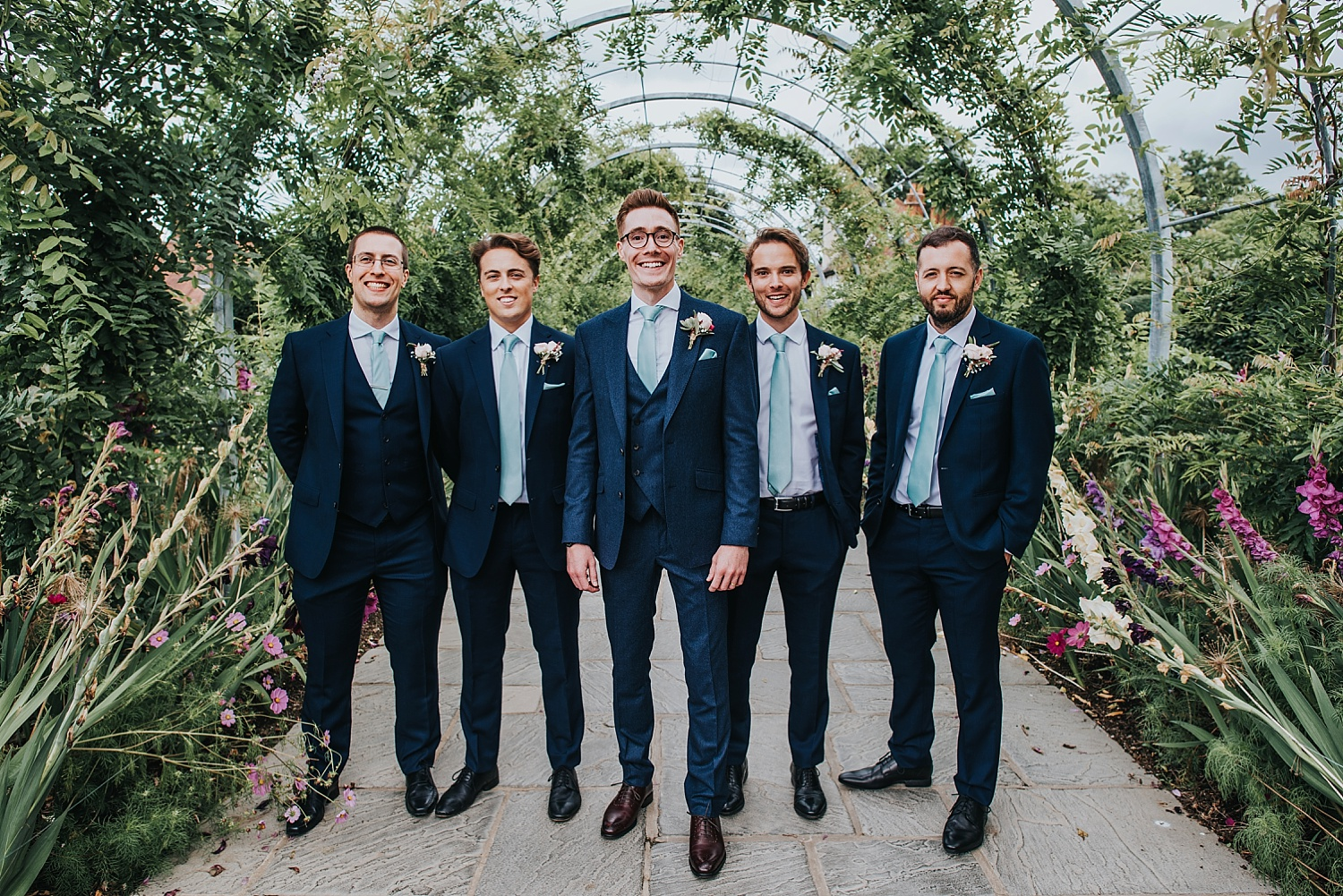 groom and groomsmen standing in the cottage garden RHS Wisley