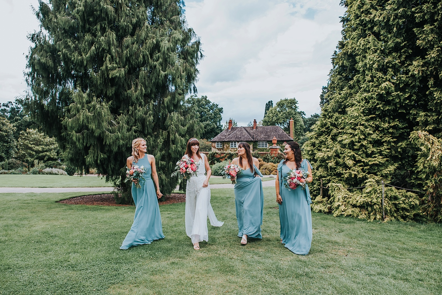 bride and bridesmaids walking to to cottage gardens RHS Wisley