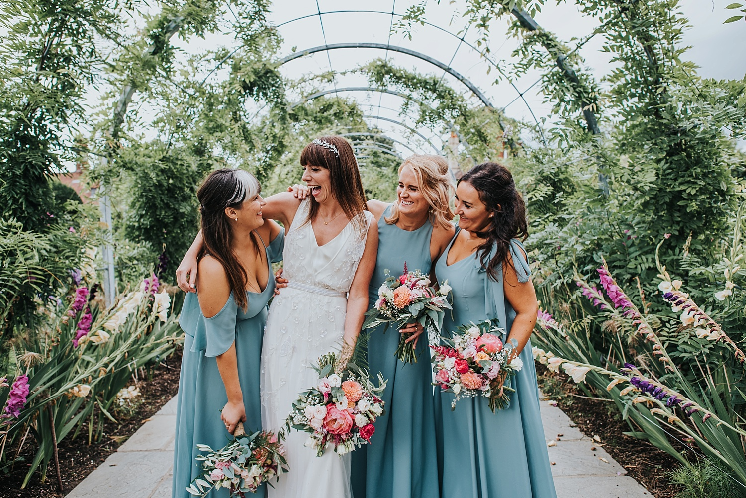 Bride and bridesmaids standing in the cottage garden RHS Wisley