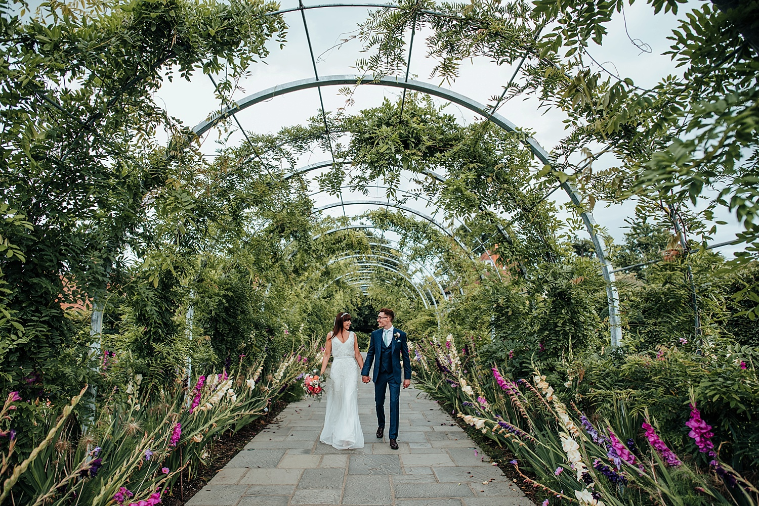 bride and groom walking through arch in RHS Wisley gardens