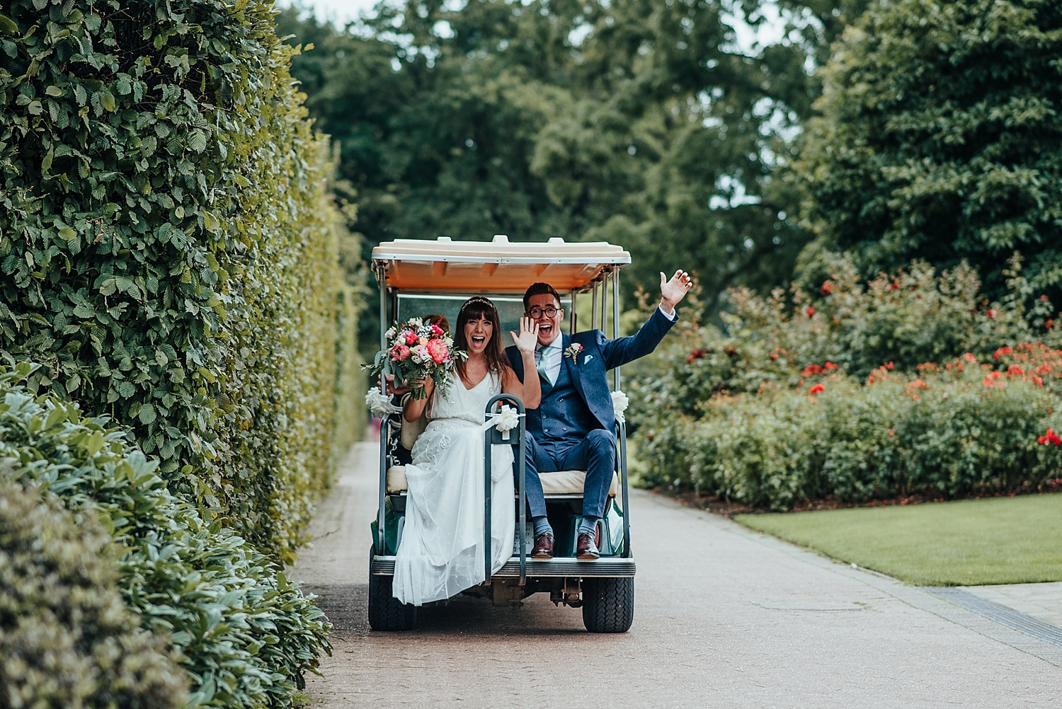 bride and groom riding a golf buggy around RHS Wisley