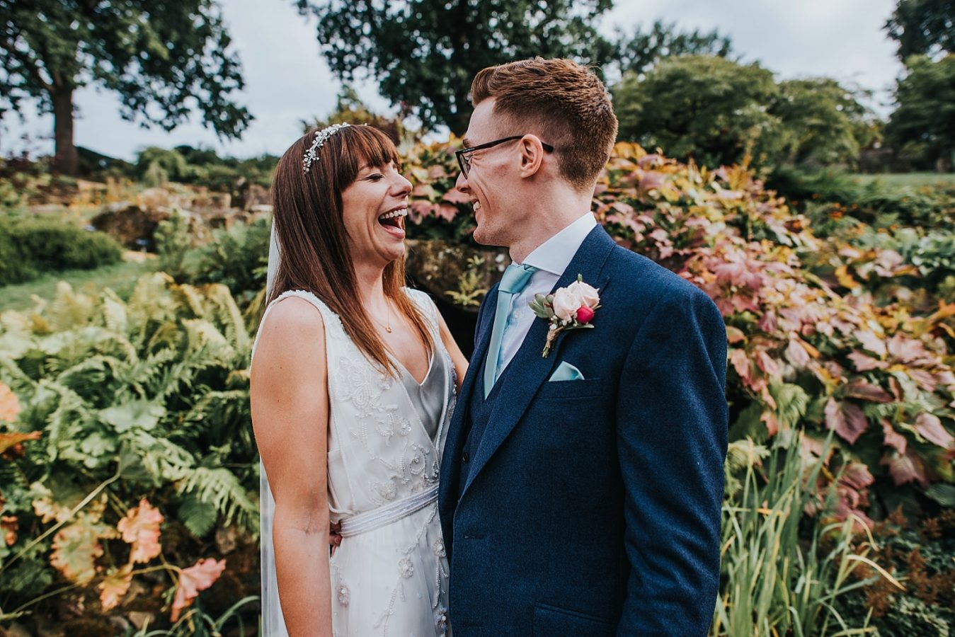 bride and groom laughing together in the rock garden RHS Wisley