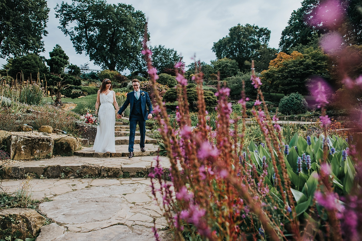 bride and groom walking through the rock garden RHS Wisley