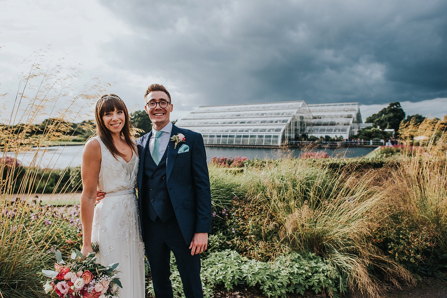 bride and groom standing by glasshouse RHS Wisley