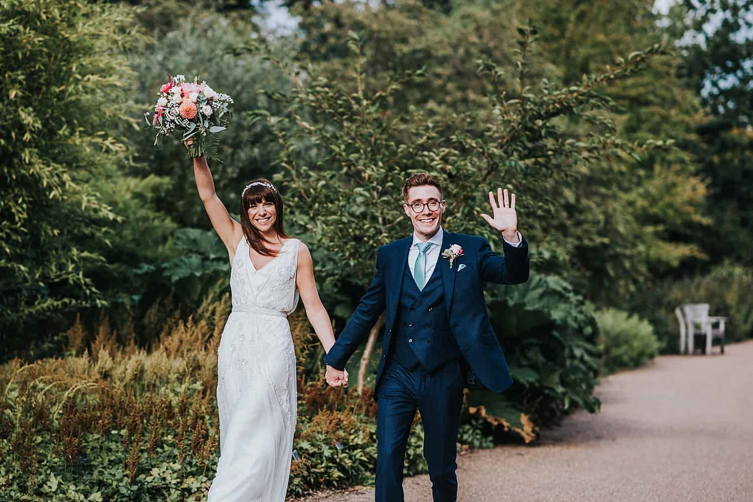 bride and groom walking with hands in the air to glasshouse RHS Wisley