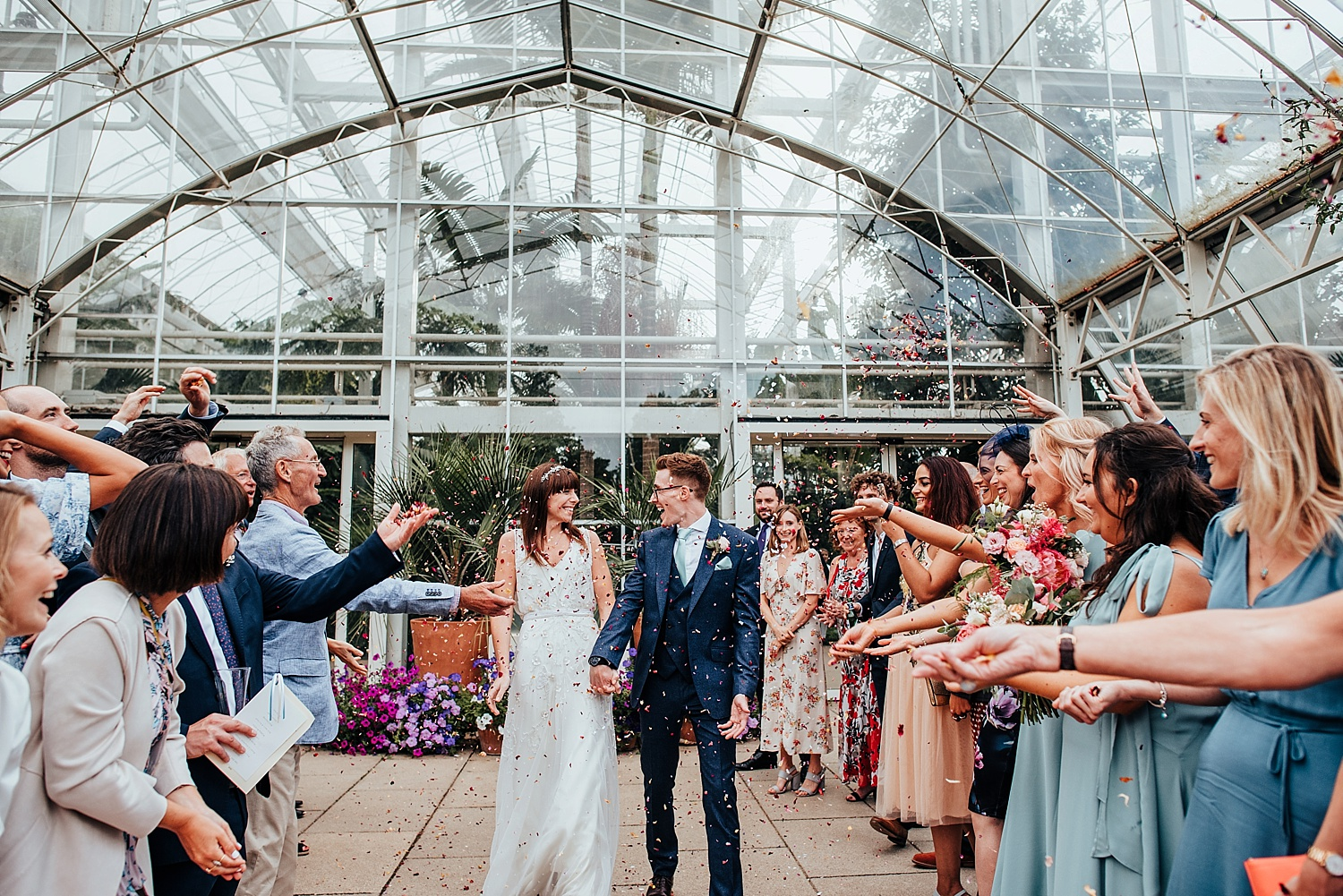 bride and groom walking through confetti outside RHS Wisley glasshouse