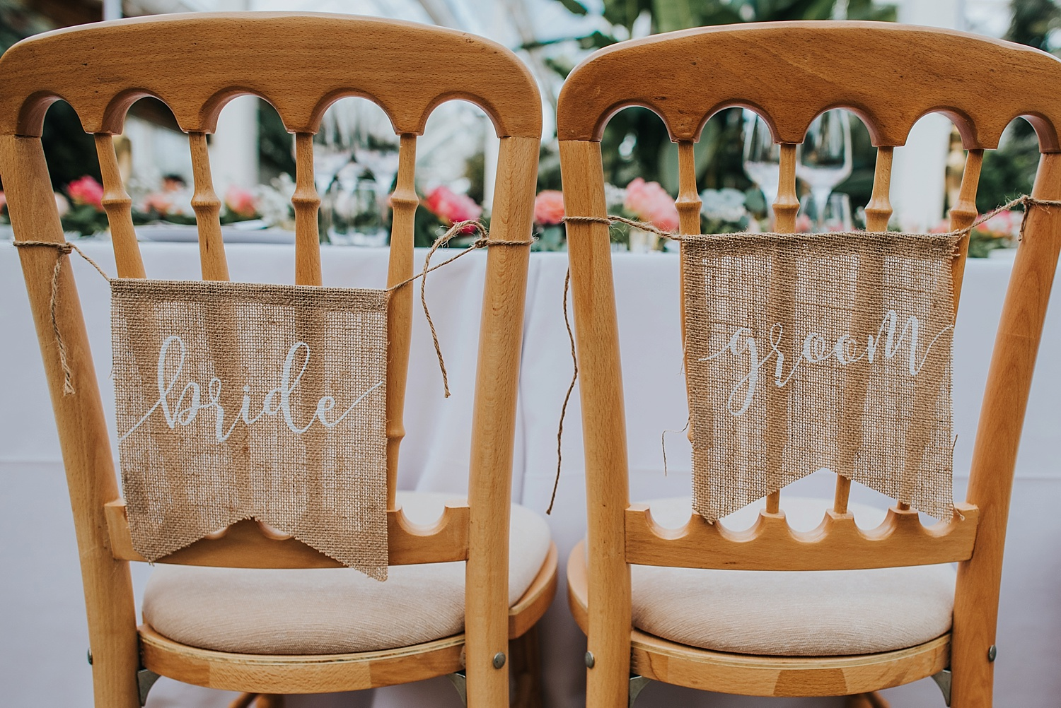 two chairs with bride and groom signs hanging down