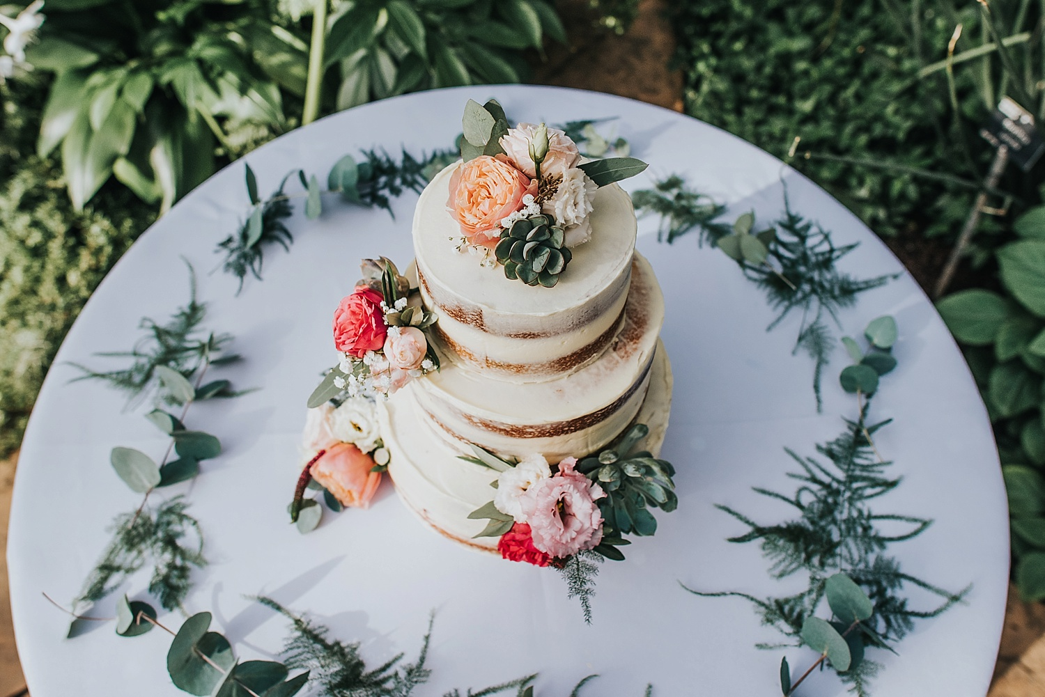 topdown view of naked wedding cake with peonies and succulents