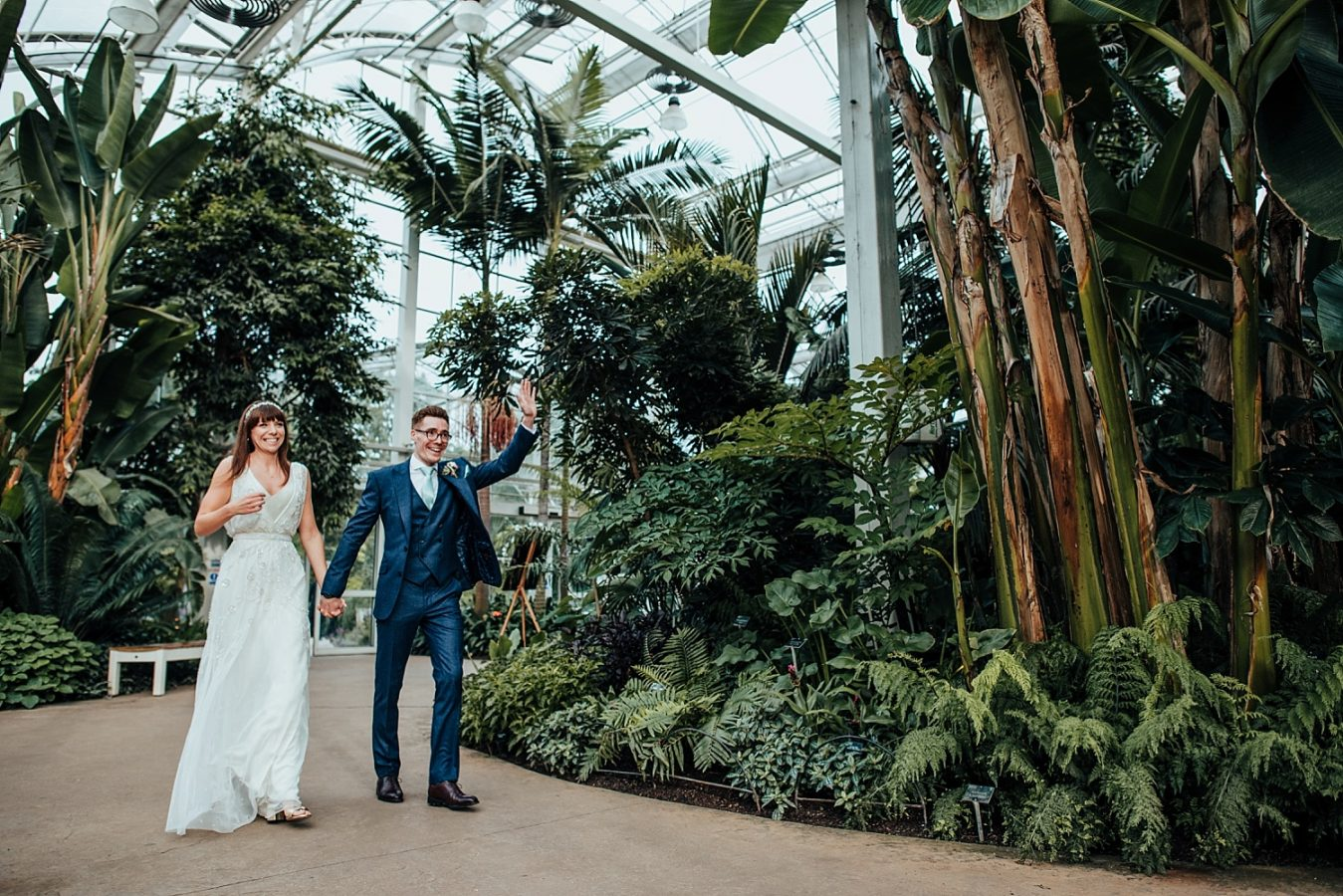 bride and groom walking into RHS WISLEY Glasshouse on wedding day